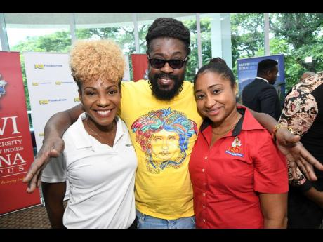 Entertainer Beenie Man is happy to be in the midst of beauties Belinda Williams (left), head of marketing and communications of PROVEN, and Venneshia Sinanan, corporate finance manager, CB Group.