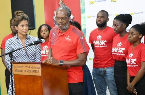 """Alfred """"Frano"""" Francis, race director, CB Group/UWI 5K, addresses the launch of the event last Wednesday at The UWI Regional Office. Scholarships were also distributed to students for the 2019-2020 school year. Looking on is Elizabeth Buchanan-Hind (left), chair of the fund-raising event to raise funds for students wishing to pursue tertiary education, but in need of financial assistance."""