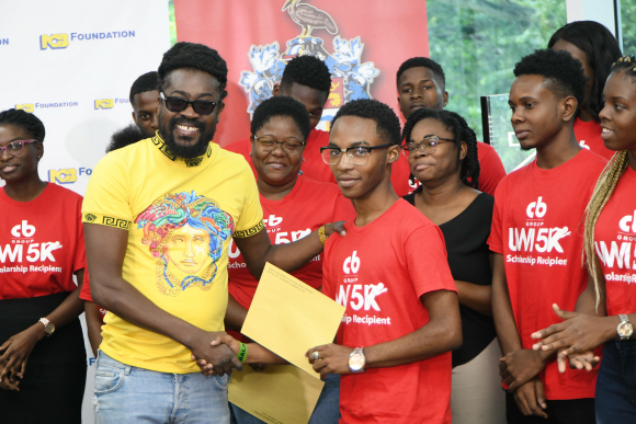 """Jhevonte Webster receiving the CB Group UWI 5K/Khadene """"Miss Kitty"""" Hylton Scholarship being presented on her behalf by Moses """"Beenie Man"""" Davis. The presentation took place at the launch of the 5K fund raising event on October 2 at the UWI Regional Headquarters."""